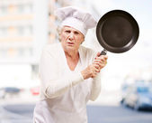 Cook senior woman angry trying to hit with pan against a buildin — Stock Photo