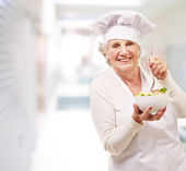 Portrait of adorable senior cook woman eating salad indoor — Stock Photo