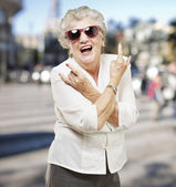 Portrait of senior woman doing rock symbol at city background — Stock Photo
