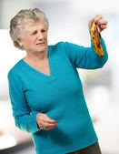 Senior mujer sosteniendo un plátano podrido interior — Foto de Stock