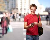Retrato de jovem homem tocando a tela do celular na rua cheia de gente — Foto Stock