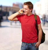 Portrait of young man talking on mobile at street — Stock Photo