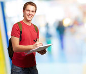 Portrait of young student man writing on a notebook at universit — Stock Photo