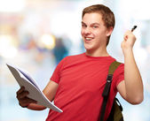 Portrait of handsome student holding notebook and pen against a — Stock Photo