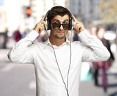 Portrait of young man listening to music using headphones at cro — Stock Photo