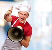 Portrait of young cook man screaming with megaphone and gesturin — Stock Photo
