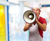 Portrait of young cook man screaming with megaphone indoor — Stock Photo