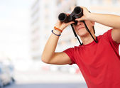 Portrait of young man with binoculars against a building — Stock Photo
