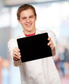 Portrait of young man showing digital tablet indoor — Stock Photo