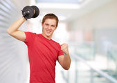 Young man doing fitness with weights at entrance of building — Stock Photo