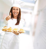 Woman chef holding baked food — Stock Photo