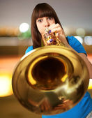 Portrait of a young girl blowing trumpet — Stok fotoğraf