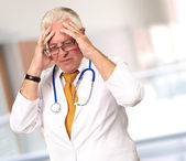 Portrait Of A Senior Doctor Holding His Head — Stock Photo