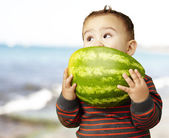 Portrait of a handsome kid holding watermelon and sucking near t — Stockfoto