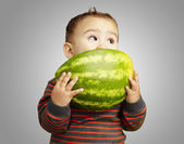 Portrait of a handsome kid holding watermelon and sucking agains — Stockfoto