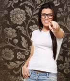 Portrait of young woman pointing with finger against a grunge wa — Stock Photo