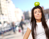 Portrait of young woman holding green apple on her head at crowd — Stock Photo