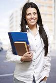 Joven y guapa mujer sonriendo y sosteniendo los cuadernos, al aire libre — Foto de Stock