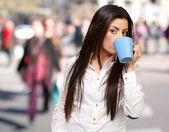 在拥挤的城市饮水的年轻女人肖像 — 图库照片