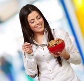 Portrait of healthy young woman eating cereals indoor — Stock Photo