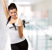 Portrait of young woman doing fitness with weights indoor — Stock Photo