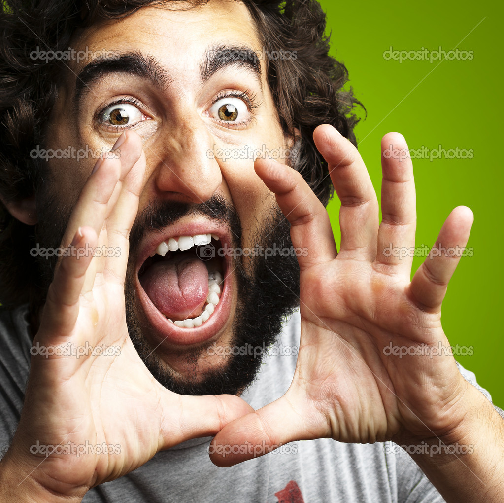 Portrait of young man screaming against a green background — Stock Photo #12092996