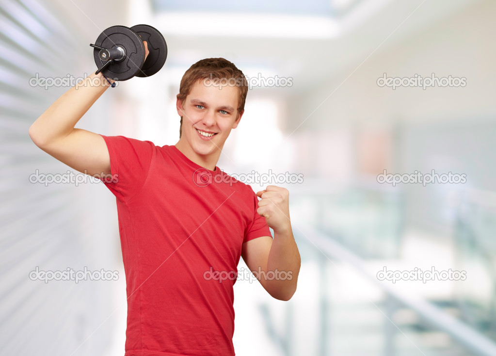 Young man doing fitness with weights at entrance of building — Stock Photo #12094274