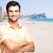 Portrait of a handsome young man standing against a beach — Stock Photo