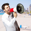 Portrait of young man screaming with megaphone against a beach — Stock Photo #12277278