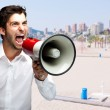Portrait of young man screaming with megaphone against a beach — Stock Photo