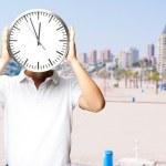 该名男子手持时钟对海滩的肖像 — 图库照片