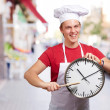Portrait of young cook man pointing a clock at street — Stock Photo #12277646
