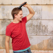Portrait of young man cutting his hair against a street wall - Stock Photo