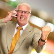 Senior Business Man Using Phone Cheering - Stock Photo