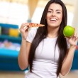 Female Holding A Piece Of Pizza And A Apple — Stock Photo #12278050