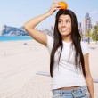 Portrait of young woman holding orange on head against a beach — Stock Photo #12278091