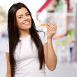 Portrait of young woman eating cereal bar at street — Stock Photo #12278136