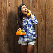Portrait of young woman talking on vintage telephone against a w — Stock Photo