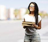 Retrato de joven sosteniendo libros en ciudad llena de gente — Foto de Stock