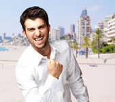 Portrait of succesful young man against a beach — Stock Photo