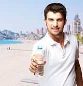 Portrait of young man offering a water bottle against a beach — Stock Photo