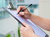 Empresário segurando uma prancheta e escrever — Foto Stock