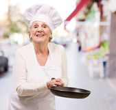 Portrait of a friendly cook senior woman holding pan at city — Stock Photo