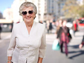 Portrait of happy senior woman wearing heart glasses at street — Stock Photo
