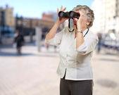 Portrait of senior woman looking through a binoculars at street — Stock Photo