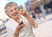 Portrait of senior woman eating chocolate and cream cup at stree — Stock Photo