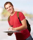 Portrait of young student man writing on a notebook at street — Stock Photo