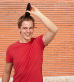 Portrait of young man cutting his hair against a bricks wall — Stock Photo