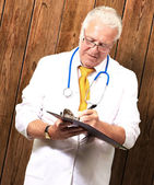 Senior Male Doctor Writing On Clipboard — Stock Photo