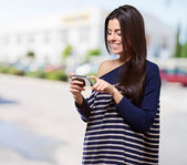 Portrait of young woman touching a modern mobile at street — Stockfoto